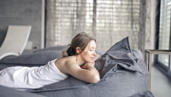 woman-in-white-tank-top-lying-on-gray-bed-3673941